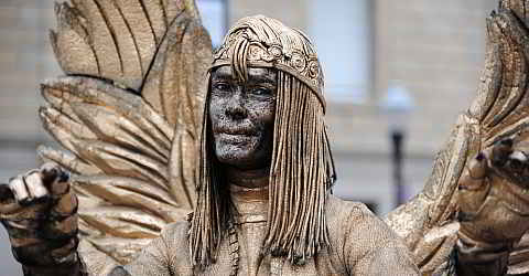 Street artists work as living statues